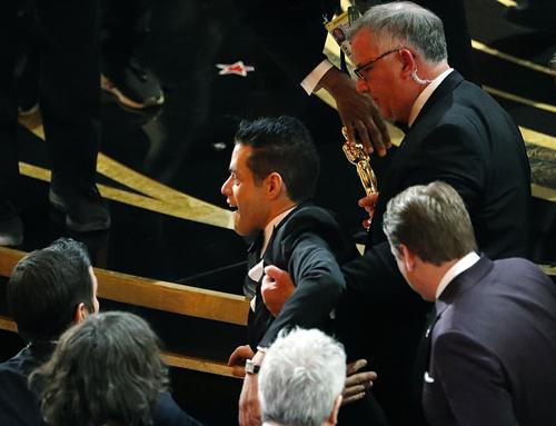 Rami Malek được đỡ dậy sau khi ngã. Ảnh: Reuters.