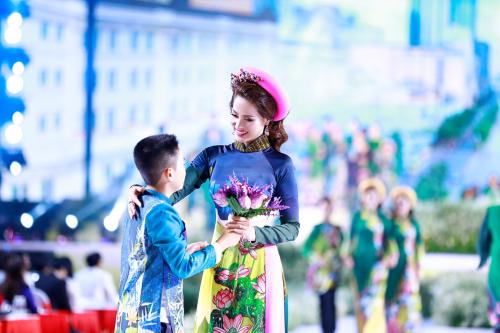Con trai á hậu mặc áo dài gấm xanh in họa tiết hoa sen đồng điệu với chi tiết trên áo dài Băng Châu.