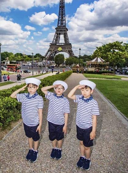 Ba con trai của Song Il Gook chụp ảnh trước tháp Afie, Paris.