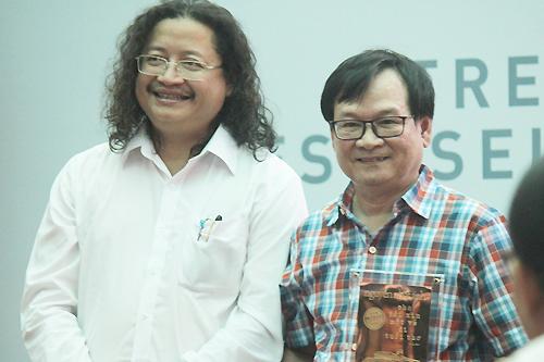 [Caption]Nguyễn Nhật Ánh (phải) nhận kỷ niệm chương cho tác giả sách bán chạy từ ông Nguyễn Minh Nhựt.