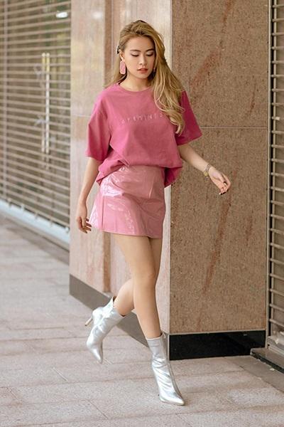 Hoàng Thùy Linh theo đuổi mốt màu hồng với chân váy ép nhựa, áo phông và khuyên tai bản lớn. Cô tạo điểm nhấn bằng đôi bốt