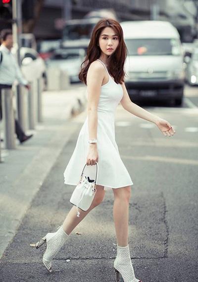 Ngọc Trinh chọn cách mặc cả bộ màu trắng tối giản gồm váy hai dây, bốt cổ ngắn và túi mini.