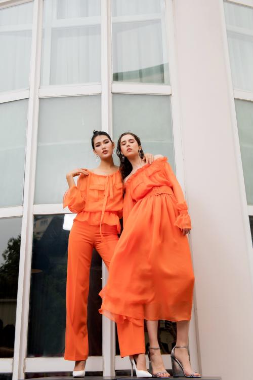 Chọn tông cam làm màu chủ đạo, bộ đôi thiết kế mang đường nét nữ tính vào váy voan dài, áo trễ vai nhún bèo mềm mại.