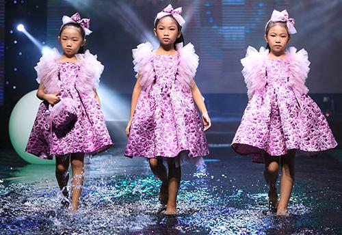 Nhóm người mẫu nhí Pinkids trình diễn thời trangtrên sân khấu nước.
