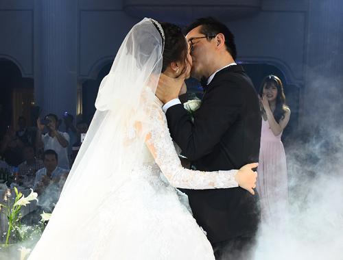 Vợ chồng nghệ sĩ trao nụ hôn trong tiệc cưới.