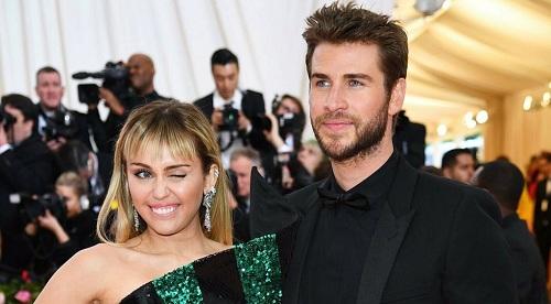 Ca sĩ Miley Cyrus tinh nghịch bên chồng, Liam Hemsworth. Đây là lần đầu tiên hai người cùng xuất hiện tại thảm đỏ Met Gala. Ảnh: Vogue.