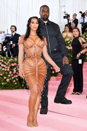 Người đẹp siêu vòng ba Kim Kardashian dự tiệc cùng chồng Kanye West. Rapper nổi tiếng, thay vì chọn những trang phục đắt tiền, mặc chiếc áo khoác đơn giản của hãng Dickies. Ảnh: Film Magic.