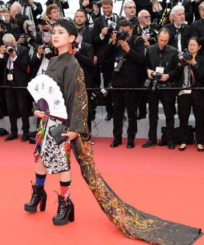 Một người cầm quạt giấy in chữ Trung Quốc chế tạo lên thảm đỏ Cannes 2019.
