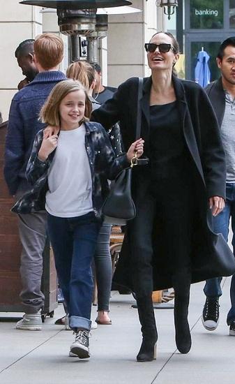 Vivienne (10 tuổi) luôn nắm chặt quai túi xách của mẹ vì sợ đi lạc. Ảnh: Hollywood Life.