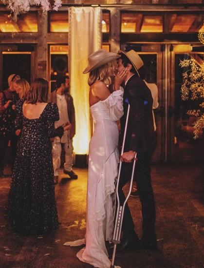 Cô dâu và chú rể hôn nhau trong buổi tiệc.