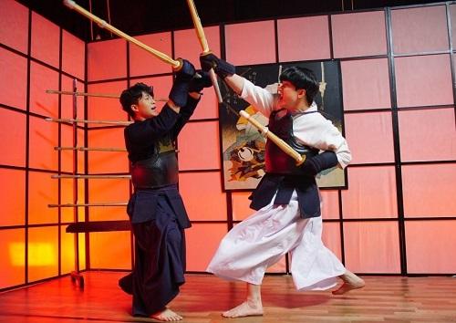 B Trần (phải) và Harry Lu đấu kiếm. Harry cho biết phải tập trung cao độ trong những cảnh này để tránh bị đánh trúng phần mặt vừa phẫu thuật.