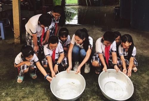 Tiểu Vy hứng nước mưa cùng học sinh.