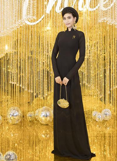 Trương Thị May chọn áo dài của nhà thiết kế Đinh Văn Thơ. Cô phối hoa tai kim loại bản to và clutch đính đá tông vàng cùng trang phục.
