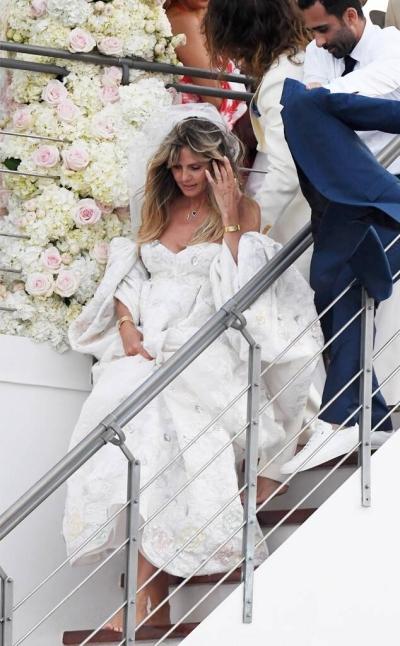 Heidi Klum chọn bộ đầm trắng cúp ngực với phần tay phồng dáng trễ vai lấy cảm hứng từ thập niên 1980.