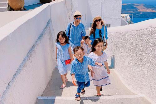 Cả nhà diện trang phục tông trắng, xanh dương, trùng với tông màu chủ đạo của kiến trúc địa phương,