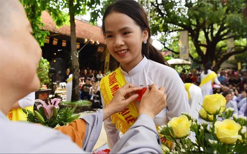 Một nữ sinh được sư thầy chùa Văn Trì (Hà Nội) cài hoa hồng đỏ lên áo trong dịp lễ Vu Lan. Ảnh: Giang Huy.