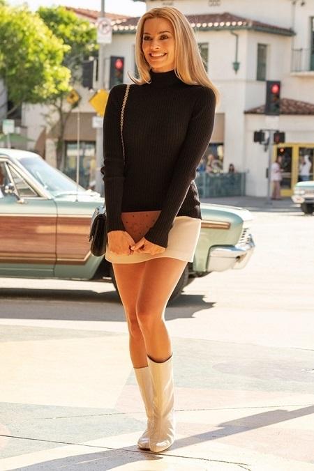 Margot Robbie diện minidress trắng và áo len cổ lọ đen trong phim. Ảnh: Sony Pictures.