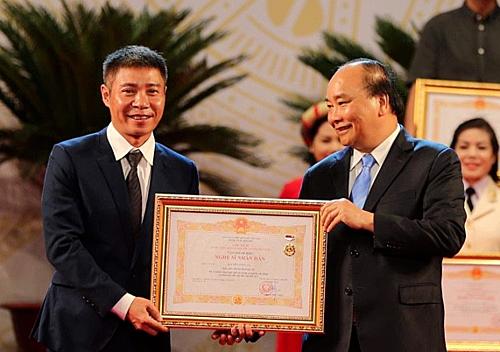 Thủ tướng Nguyễn Xuân Phúc trao bằng chứng nhận danh hiệu Nghệ sĩ Nhân dân cho diễn viên Công Lý (trái).