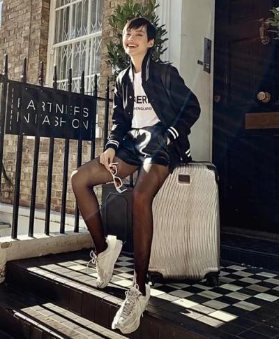 Khánh Linh The Face chọn mốt quần shorts da những năm 1990 với áo khoác bóng chày.