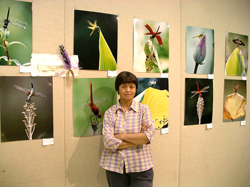 Bà Châu Thông Linh bên các bức ảnh chụp chuồn chuồn. Ảnh: Hk01.