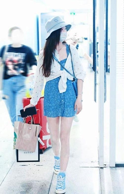 Âu Dương Na Na mix đôi Converse xanh dương với váy ngắn hai dây họa tiết cùng màu. Người đẹp tạo điểm nhấn với một chiếc sơ mi thắt nút bên ngoài. Tổng thể trang phục đem đến cho Na Na vẻ trẻ trung, hiện đại.