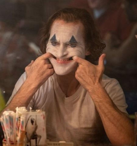 Một cảnh Joaquin Phoenix kết hợp động tác hình thể và hóa trang để gây sợ hãi. Ảnh: Warner Bros.