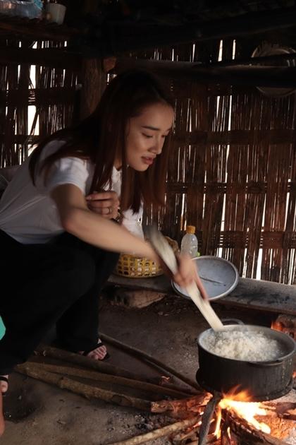 Nhã Phương thổi cơm sau khi đi mua thức ăn cho gia đình chị Y Mê.