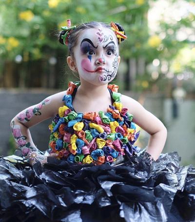 Cô bé được vẽ mặt kiểu chú hề, mặc trang phục từ bóng bay, túi nilon.