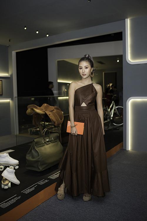 Quỳnh Anh Shyn diện chiếc váy lệch vai màu nâu, cắt khoét khéo léo. Người đẹp tạo dáng bên những vật phẩm được trưng bày tại sự kiện.