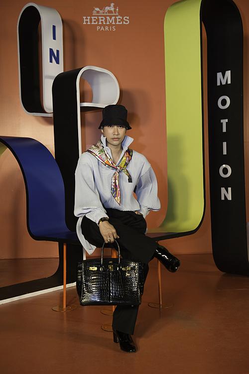 Lý Quí Khánh -một trong những người nổi tiếng trong giới thời trang tại Việt Nam cũng không bỏ qua cơ hội tìm hiểu về lịch sử của thương hiệu anh yêu thích. Nhà thiết kế 8x diện quần đen kết hợp với áo sơ mi cách điệu sáng màu và tạo điểm nhấn bằng khăn quàng cổ màu sắc rực rỡ cùng túi xách Hermès.
