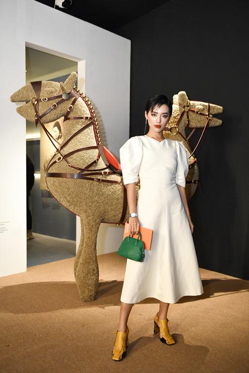 Người mẫu Khánh Linh The Face chọn bộ váy dáng dài màu trắng thanh lịch kết hợp cùng sandal cao gót vàng và túi xanh đậm. Cô chụp ảnh cùng mô hình ngựa hai đầuvới yên và dây cương - những sản phẩm khởi nguồn của thương hiệu nổi tiếng của Pháp.