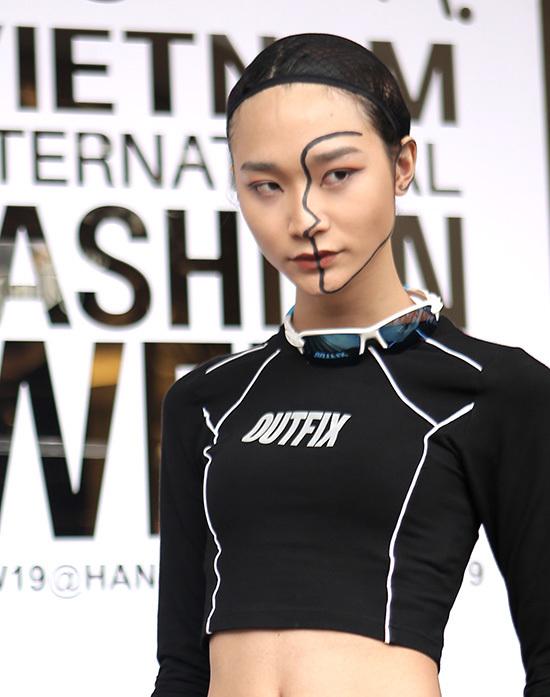 Ashley Nguyễn dùng tông đỏ đất cho mắt và môi. Cô gái kẻ viền đường nét khuôn mặt tôn nét thanh thoát.