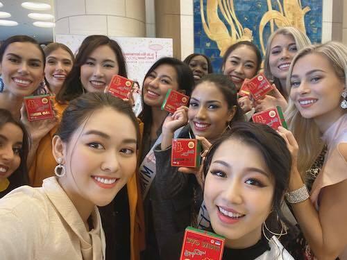 Tường San (trái, hàng đầu) tặng bánh cốm cho các thí sinh Miss International. Ảnh: SV.