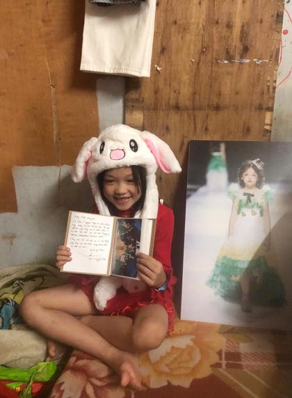 Bé Hoàng Anh bên bức ảnh và cuốn album mới được in tặng. Ảnh: TN.