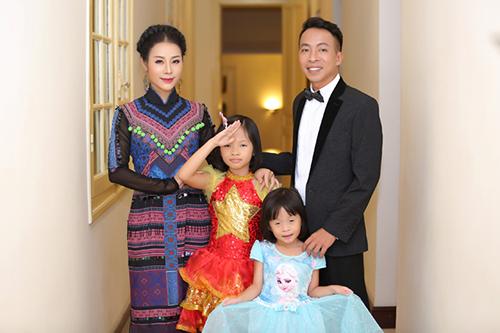 Bé Nghé (con gái thứ hai, váy đỏ) và bé Mún (con gái út, váy xanh) - cùng bố mẹ tham gia một chương trình ca nhạc. Ảnh: HòaNguyễn.