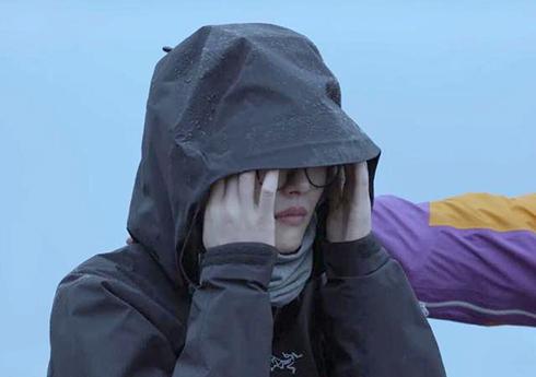 Lưu Văn kéo mũ áo che nước mắt trong chương trình. Ảnh: QQ.