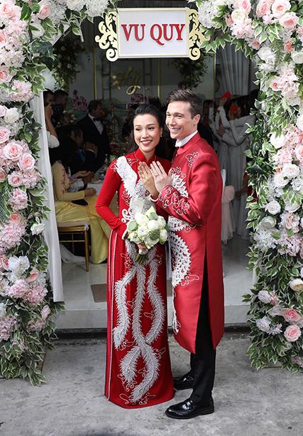 Hoàng Oanh diện áo dài thêu chim phụng đồng điệu với chồng.