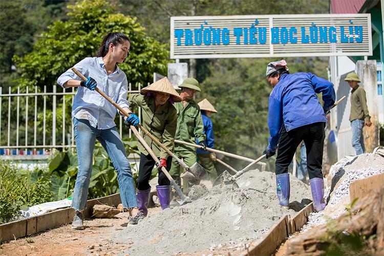 Hoa hậu Thùy Linh (trái) cùng người dân xây đường. Ảnh: SV.