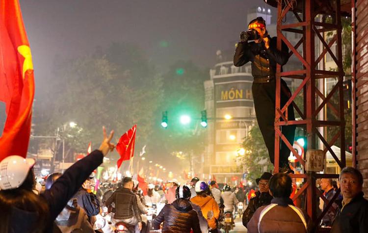 Để có những khoảnh khắc đẹp, nghệ sĩ leo lên cột điện để chụp khiến người đi đường chú ý.