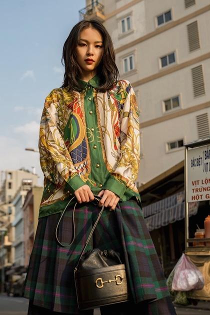 Quán quân The Face Phí Phương Anh cũng bắt kịp xu hướng với dòng túi mới. Cô phối túi chiếc xô với áo sơ mi họa tiết vương giả, quần kẻ sọc theo phong cách thu đông.