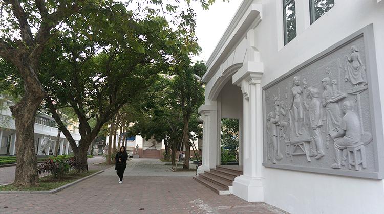Bức phù điêu được gắn trên tường tòa nhà ngay cạnh lối vào trường. Ảnh: Hiểu Nhân.