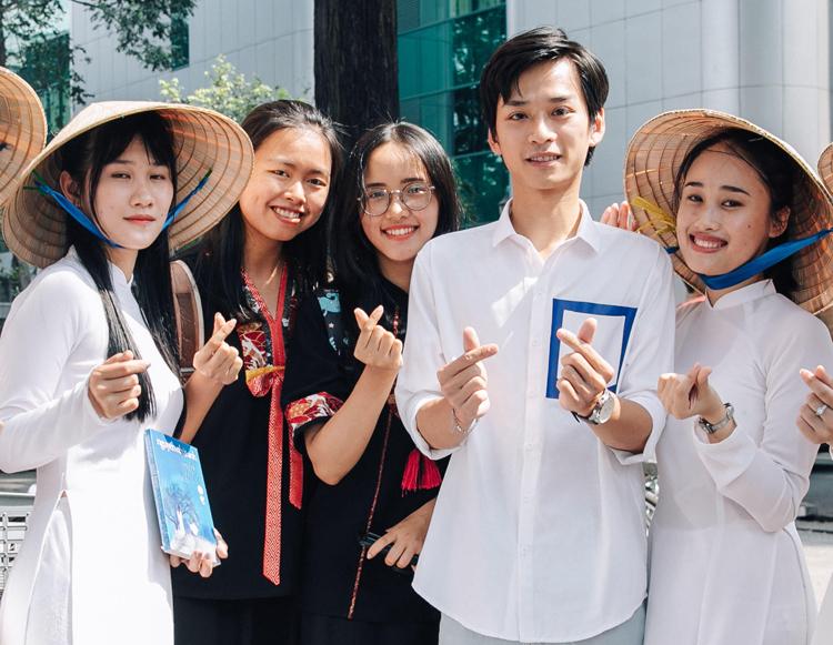 Độc giả mặc áo dài trắng chụp ảnh cùng Trần Nghĩa. Ảnh: Khôi Trần.