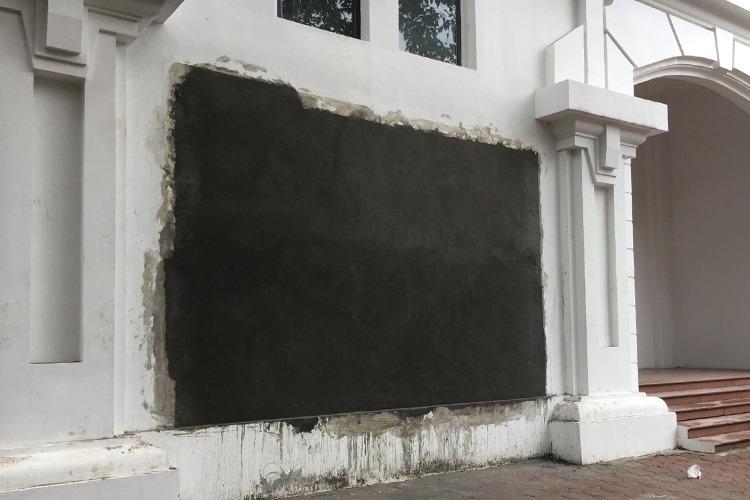 Phù điêu trên tường tòa nhà ngay cạnh lối vào trường đã gỡ bỏ. Lớp xi măng màu đen sẽ được sơn trắng để đảm bảo cảnh quan nhà trường. Ảnh: M.T.