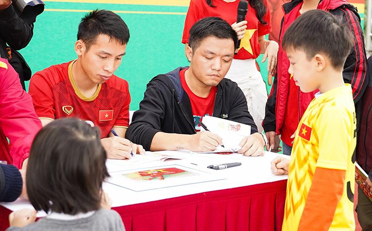 Cầu thủ Hùng Dũng (trái) ký tặng cho các em nhỏ tại buổi họp báo ra mắt sách sáng 5/1. Ảnh: NXB Kim Đồng.