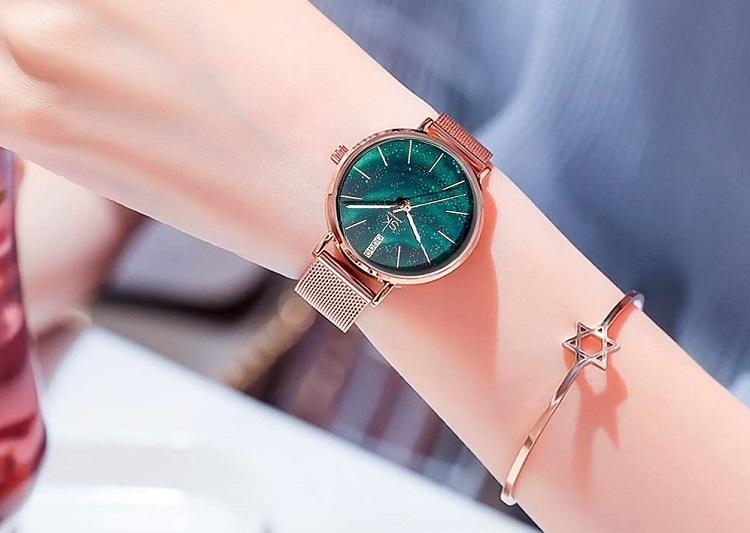 Đồng hồ nữ thương hiệu Shengke Korea 11K0103L-01 có mặt số cách màu xanh lá bắt mắt, lấy cảm hứng từ hình ảnh bầu trời sao ban đêm. Đường kính mặt đồng hồ 32 mm, vừa với cổ tay phái nữ. Chất liệu vỏ làm từ hợp kim brass, màu vàng hồng, không gỉ. Góc 12 giờ đính 4 viên đá thay cho vạch số. Logo thương hiệu in giữa mặt số. Sản phẩm được bảo hành chính hãng 12 tháng, thay pin miễn phí lần đầu. Đồng hồ có giá 1,199 triệu đồng, giảm 50% so với giá gốc.