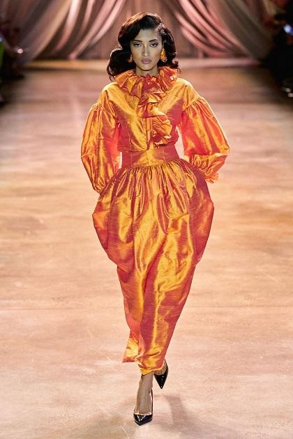 Nhiều chi tiết trên BST lấy cảm hứng từ trang phục rạp xiếc: cổ áo xếp ly, bèo nhún, quần ngoại cỡ tạo cảm giác như váy, váy sơ-mi, đầm dây rút, jumpsuit, tất chân màu sắc,... Ảnh trên là bộ cánh cách điệu màu cam, mở màn show diễn, phần thân trên và dưới đều được làm phồng lên với cổ áo xếp ly; gợi lên hình ảnh chú hề trong điện ảnh Pháp.