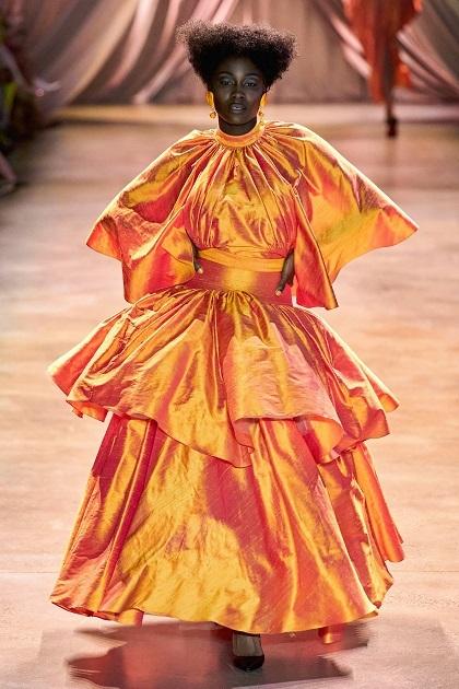 Nhà mốt người Pháp Madame Grès trong giai đoạn năm 1960–1980, chuyển trọng tâm thời trang từ váy nữ thần sang trang phục mang cảm hứng hình học. Những thiết kế của bà giai đoạn này truyền cảm hứng cho Roges về kết cấu trang phục. Anh thường sử dụng những đường chiết eo, xếp ly, trang phục độn, xếp tầng, tạo khung,... để dựng kết cấu. Trong ảnh, người mẫu Aba Mfrase Ewur mặc váy màu cam kẹo ngọt xếp tầng.