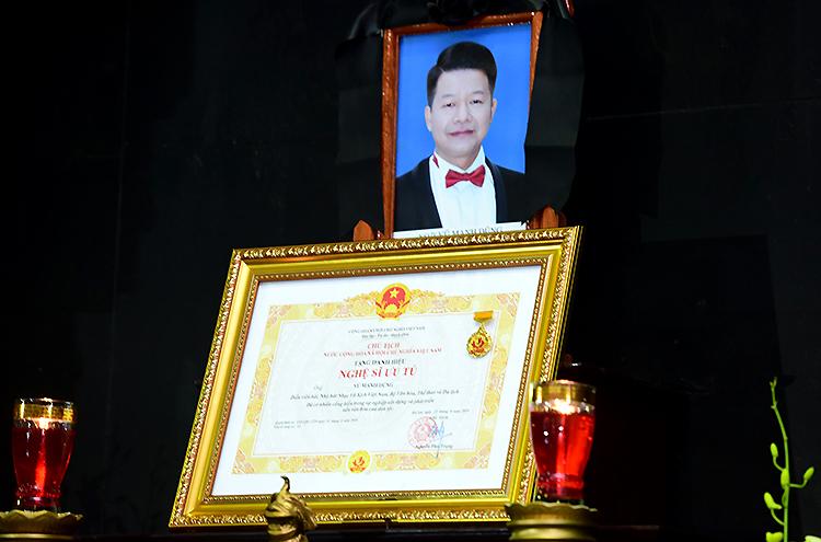 Ca sĩ Vũ Mạnh Dũng nhận danh hiệu Nghệ sĩ Ưu tú tháng 8 năm ngoái. Tấm bằng được người thân đặt trước di ảnh anh trong lễ tang chiều 20/2. Ảnh: Giang Huy.