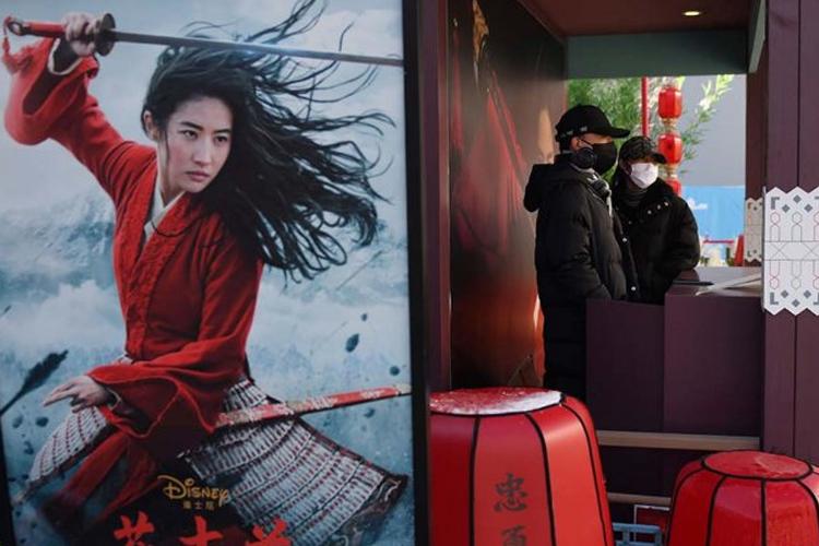 Hai nhân viên đeo khẩu trang (phải) tại bốt quảng cáo phim Mulan tại Bắc Kinh. Ảnh: AFP.