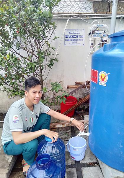 Người dân miền Tây bên máy lọc nước mặn được tặng. Ảnh: